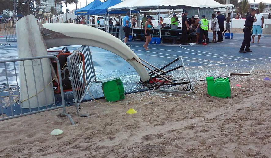 In this photo provided by Burt Osteen, glass is scattered around a toppled basketball hoop after a waterspout made landfall at Fort Lauderdale Beach, Fla. on Monday, May 25, 2015. Authorities say three children were injured when the waterspout uprooted a bounce house and sent it across a parking lot into the road. (Burt Osteen via AP)