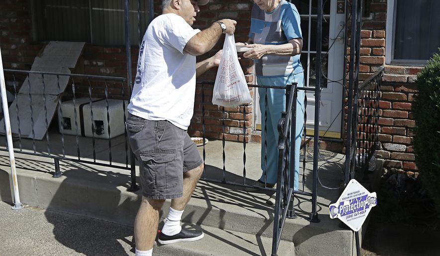 In this Thursday, May 7, 2015 photo, Bob Gill, a volunteer driver with Meals on Wheels By ACC, delivers lunch to Thelma Pense at her home in Citrus Heights, Calif. Meals on Wheels by ACC provides free meals to senior citizens at a senior center and brings them meals at their homes. Meals on Wheels is among the programs that have received funds from the state Assembly's own administrative budget for programs that faced cuts in state and other funding. (AP Photo/Rich Pedroncelli)