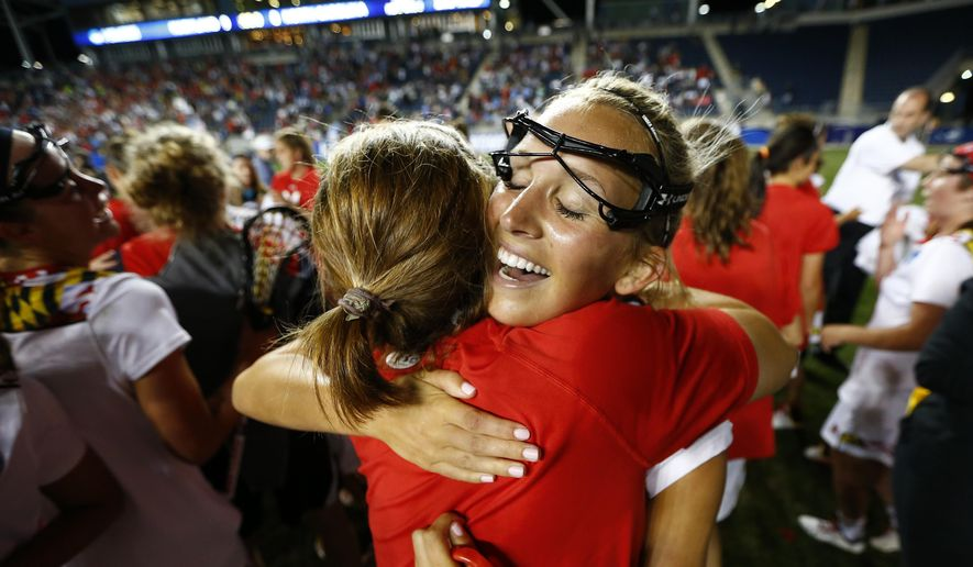 Maryland's Kristen Lamon, right, hugs a teammate after defeating North Carolina 9-8 in the championship match in the NCAA Division I women's lacrosse tournament, Sunday, May 24, 2015, Chester, Pa. (AP Photo/Rich Schultz)