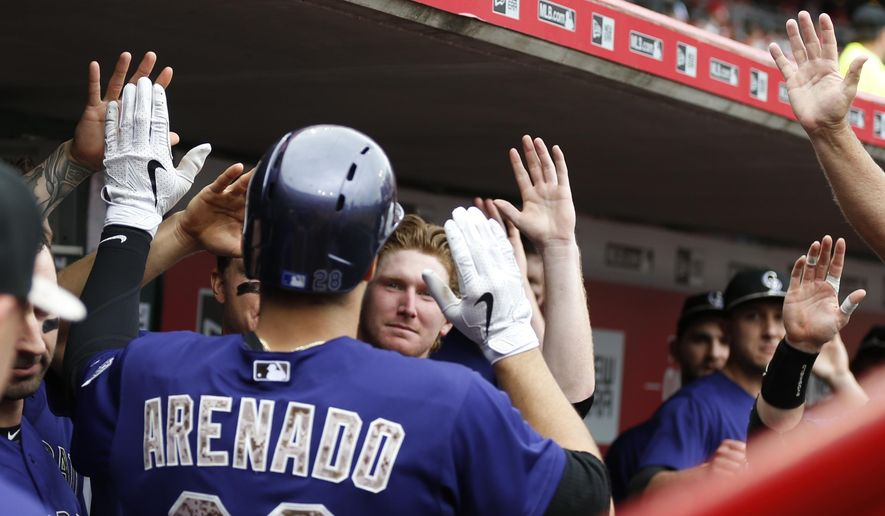 Colorado Rockies' third baseman Nolan Arenado (28) is congratulated by teammates following a solo home run off Cincinnati Reds' starting pitcher Jason Marquis (31) during the fourth inning of their baseball game Monday, May 25, 2015,  in Cincinnati. (AP Photo/Gary Landers)