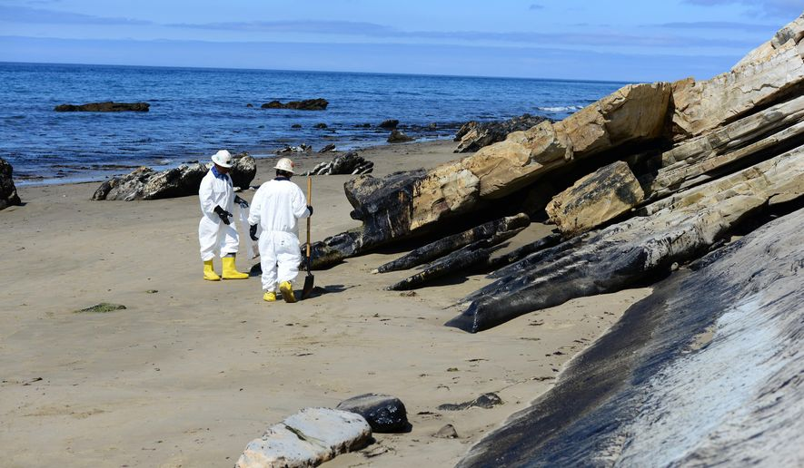 In this Saturday, May 23, 2015 photo released by the U.S. Coast Guard, two cleanup crew members work to remove oil from the sand along a portion of soiled coastline near Refugio State Beach,  north of Goleta, Calif. Oil spilled from a pipeline resulted in the cleanup efforts at the onshore site and along several miles of California coastline. (Chief Petty Officer David Mosley/U.S. Coast Guard via AP)