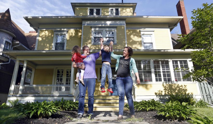 """In this May 14, 2015 photo, Jamie, second left, and Kelly Rye, right, pose for photos with their children Jane, 2, left, and Jonah, 5, in front of their 3,400-square-foot home in Toledo, Ohio. The Ryes will soon move out of their 3,400-square-foot home, which sold after only a little advertising on a private neighborhood Facebook page, and into a 400-square-foot """"tiny house."""" (Amy E. Voigt/The Blade via AP)  MANDATORY CREDIT; MAGS OUT; NO SALES; TV OUT; SENTINEL-TRIBUNE OUT; MONROE EVENING NEWS OUT; TOLEDO FREE PRESS OUT"""