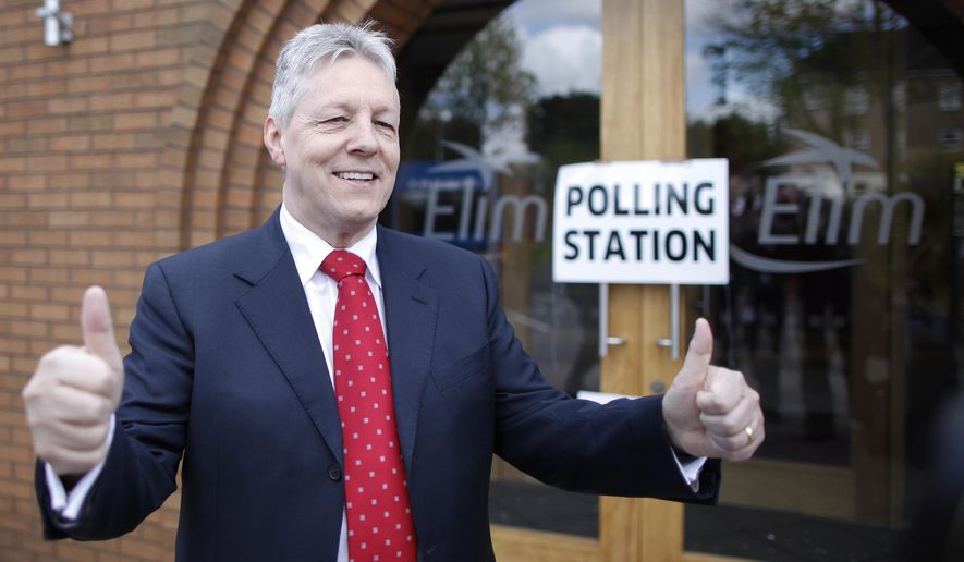 FILE- In this file photo dated  Thursday, May 7, 2015, Northern Ireland First Minister and leader of the Democratic Unionist Party Peter Robinson gives the thumbs up to waiting media after casting his vote in the General Election in East Belfast, Northern Ireland.  According to his political party, 66-year old Peter Robinson, has been hospitalized in northern Ireland after a suspected heart attack, and will remain in hospital for further tests. (AP Photo/Peter Morrison, FILE)