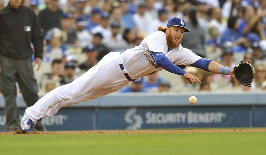 Los Angeles Dodger third baseman Justin Turner dives, but he can't come up with the ball on a single through the infield by Atlanta Braves Jonny Gomes during the fourth inning of a baseball game in Los Angeles, Monday, May 25, 2015. (AP Photo/Richard Hartog)