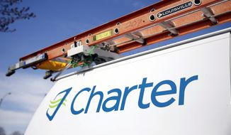This April 1, 2015, photo shows a Charter Communications van in St. Louis. Charter Communications is close to buying Time Warner Cable for about $55 billion, two people familiar with the negotiations said Monday, May 25, 2015. (AP Photo/Jeff Roberson)