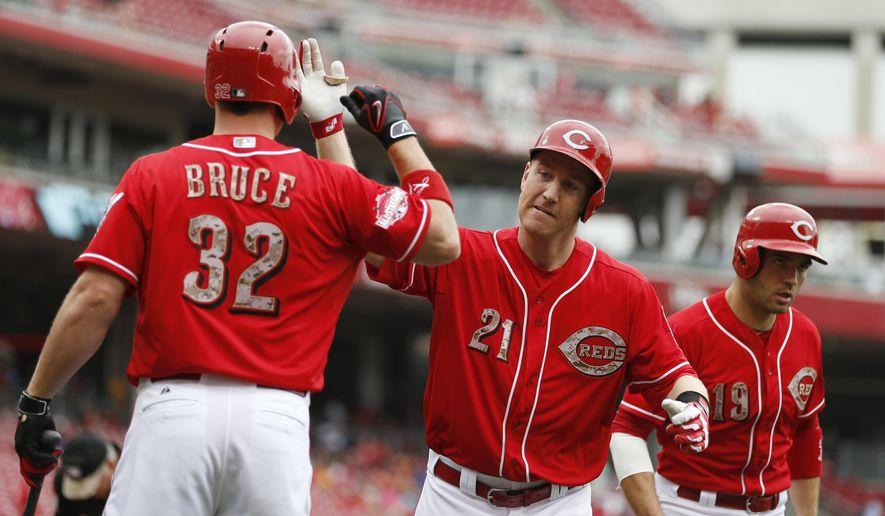 Cincinnati Reds' third baseman Todd Frazier (21) celebrates his two-run homer with Jay Bruce (32), and Joey Votto (19) off Colorado Rockies' starting pitcher Eddie Butler (31) during the first inning of their baseball game Monday, May 25, 2015, in Cincinnati. (AP Photo/Gary Landers)