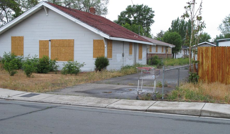 FILE - This May 15, 2015, file photo, shows the boarded duplex where Wayne Burgarello fatally shot an unarmed trespasser in February 2014, in Sparks, Nev. Burgarello now faces murder charges. The case has helped renew discussions about stand-your-ground laws and how they are interpreted across the U.S. (AP Photo/Scott Sonner, File)
