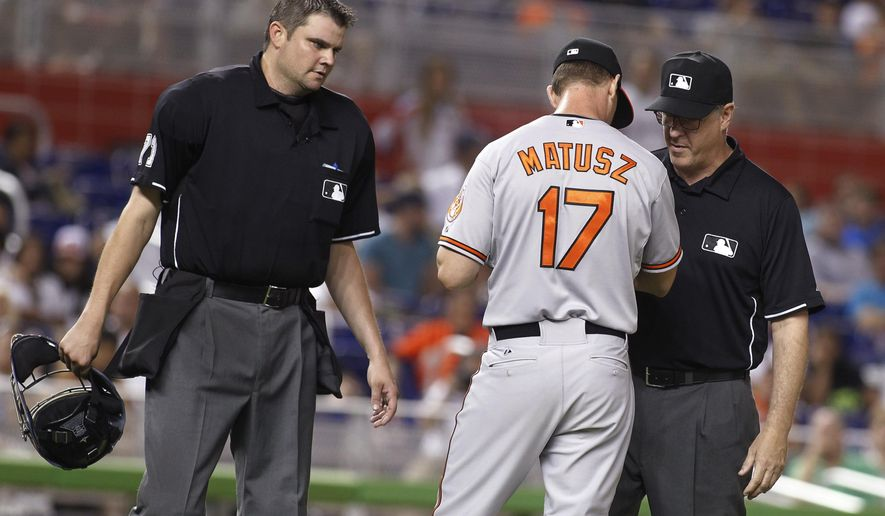 Baltimore Orioles relief pitcher Brian Matusz (17) speaks with umpires Paul Emmel, right,and Jordan Baker, left, in the 12th inning during a baseball game in Miami, Saturday, May 23, 2015. Matusz left the game after his forearm was inspected. (AP Photo/Joe Skipper)