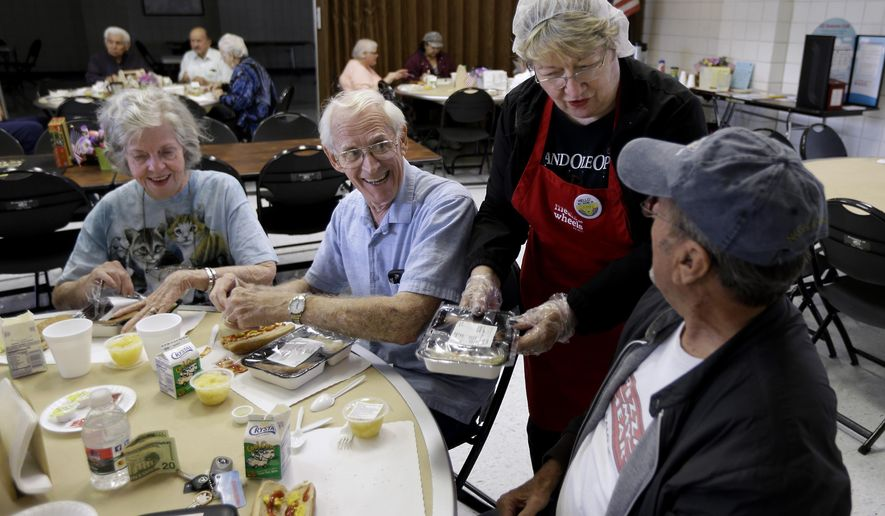 In this Thursday, May 7, 2015 photo, volunteer Sandy Lockhart, standing, serves lunch to John Pearson, right, as Dorothy Christian, left, and her husband, Fredrick, look on at a seniors meal program at the Rush Park Community Center in Citrus Heights, Calif.  The program, run by the Meals on Wheels by ACC, provides free meals to senior citizens at the center and brings them meals at their homes. Meals on Wheels is among the programs that have received funds from the state Assembly's own administrative budget for programs that faced cuts in state and other funding. (AP Photo/Rich Pedroncelli)