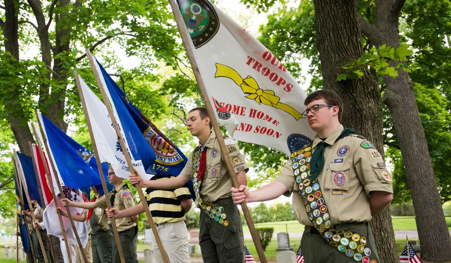 In this file photo, attendees of Boy Scouts of America stand in a line for the opening flag ceremony, Monday, May 25, 2015, at Oak Ridge Cemetery, in Bay City, Mich. (Amanda Ray/The Bay City Times via AP) **FILE**