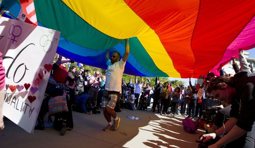 Demonstrators hold up a rainbow flag in front of the Supreme Court in Washington on April 28. The issue of same-sex marriage, which worked to the GOP's political advantage a decade ago, has flipped, with a record 60 percent of Americans now supporting it, according to Gallup polling released Wednesday. (Associated Press)