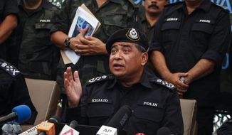 Malaysian National Police Chief Khalid Abu Bakar speaks at press conference in Wang Kelian, Malaysia on Monday, May 25, 2015. Malaysian authorities said Monday they have discovered 139 suspected graves in a series of abandoned camps used by human traffickers on the border with Thailand where Rohingya Muslims fleeing Myanmar were believed to have been held. (AP Photo/Joshua Paul)