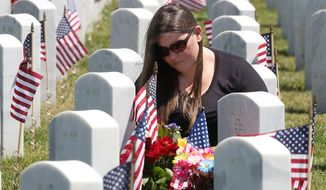 Tonya Smith visits the grave of her grandfather, Air Force veteran Tom Logsdon, at the Sacramento Valley National Cemetery in Dixon, Calif., Monday May 25, 2015. Americans observe Memorial Day to remember the men and women who died while serving in the U.S. military. (AP Photo/Rich Pedroncelli)