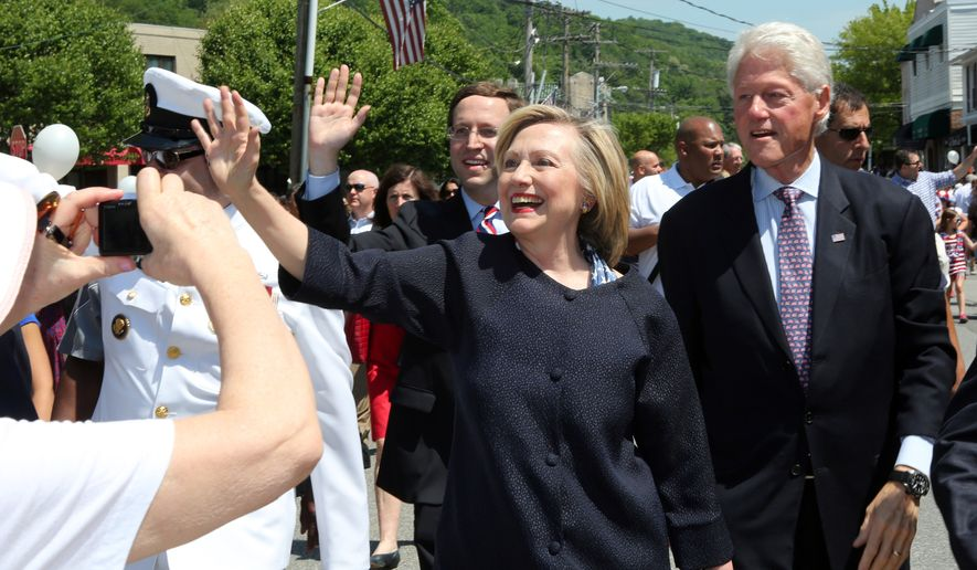 Democratic presidential candidate Hillary Rodham Clinton, center, and her husband, former President Bill Clinton, march in a Memorial Day Parade, Monday, May 25, 2015 in Chappaqua, N.Y. Close to a thousand onlookers crowded the parade route in Chappaqua, the Clinton's hometown. (Joe Larese/ The Journal News via AP) NYC OUT, NO SALES, ONLINE OUT, TV OUT, NEWSDAY INTERNET OUT; MAGS OUT