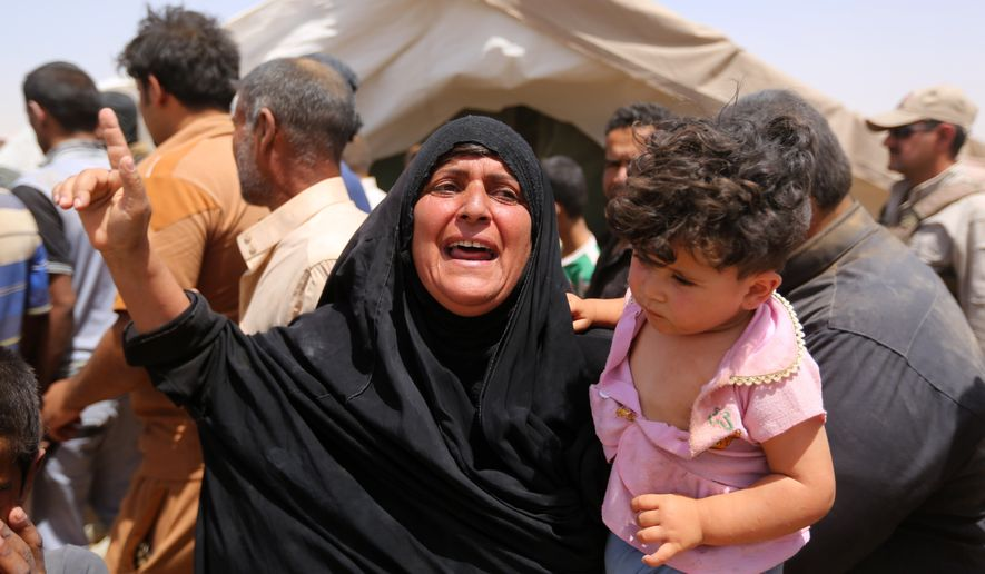 A woman who fled Ramadi holds a child in a camp in the town of Amiriyat al-Fallujah, Iraq, on Friday. (Associated Press)