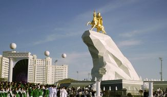 People gather for the monument unveiling ceremony in Ashgabat, Turkmenistan Monday, May 25, 2015. (AP Photo/Alexander Vershinin)