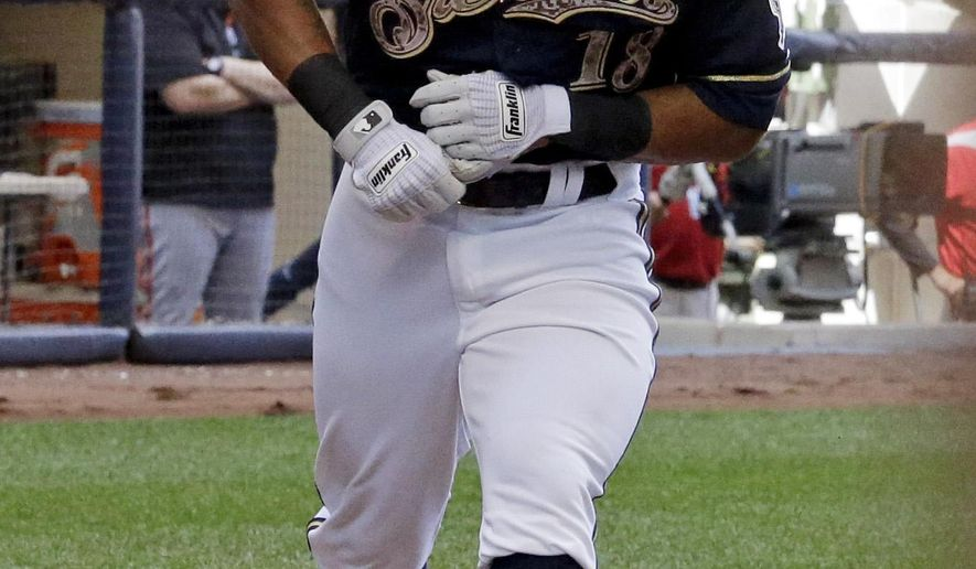 Milwaukee Brewers' Khris Davis makes a point to touch home plate after hitting his second home run of the game during the third inning of a baseball game against the San Francisco Giants Monday, May 25, 2015, in Milwaukee. (AP Photo/Morry Gash)