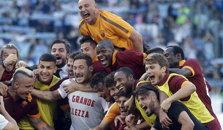 Roma's Francesco Totti, center, wears a jersey reading in Italian ' La Grande Bellezza ' (The Great Beauty) as he celebrates with his teammates at the end of a Serie A soccer match between Lazio and Roma, at Rome's Olympic Stadium, Monday, May 25, 2015. Roma won 2-1. (AP Photo/Gregorio Borgia)