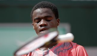 USA's Frances Tiafoe throws his racket as he plays Slovakia's Martin Klizan during their first round match of the French Open tennis tournament at the Roland Garros stadium, Monday, May 25, 2015 in Paris,  (AP Photo/Francois Mori)