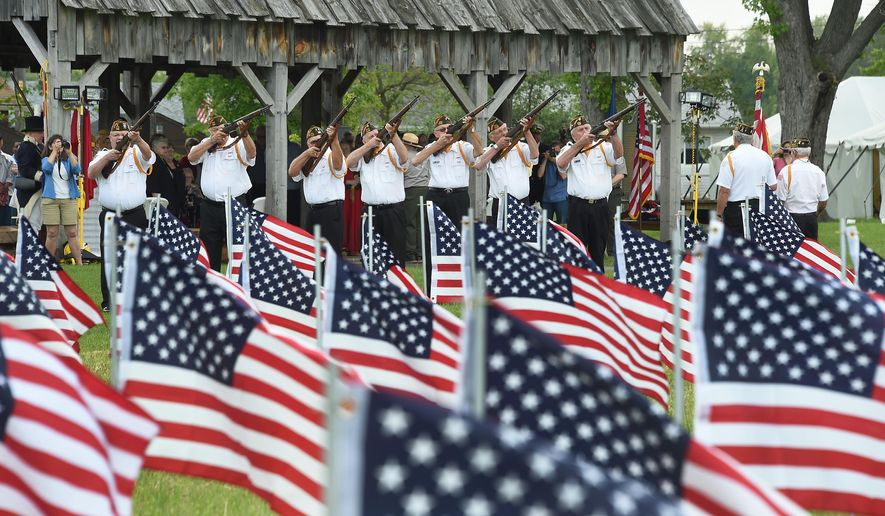 The Monroe VFW 1138 provides a gun salute during the River Raisin National Battlefield Park Field of Flag Memorial ceremony Sunday, May 24, 2015, in Monroe, Mich. (Tom Hawley/The Monroe Evening News via AP)