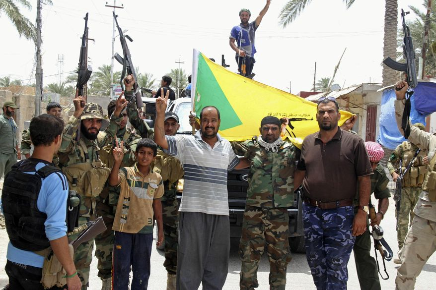 Local residents and Sunni tribal fighters welcome newly arriving Iraqi Shiite Hezbollah Brigade militiamen, brandishing their flag, who are joining the fight against Islamic State group militants in Khalidiya, 100 kilometers (60 miles) west of Baghdad, Iraq. (AP Photo)