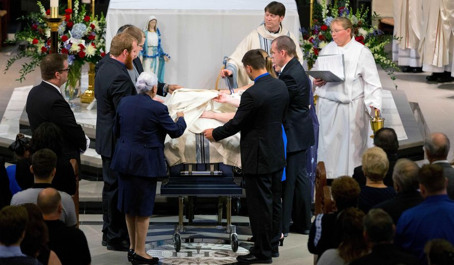 Family members cover the coffin of Omaha police detective Kerrie Orozco during funeral services at St. John's Catholic Church at Creighton University, Tuesday, May 26, 2015 in Omaha, Neb. Orozco was shot to death Wednesday by a fugitive who was fatally wounded by another officer. (Matt Miller/The World-Herald via AP, Pool)