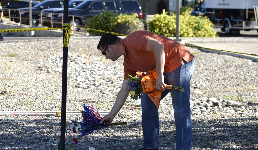 A man leaves flowers on Tuesday, May 26, 2015 near the site where authorities say a Rio Rancho police officer was shot late Monday during a traffic stop in the Albuquerque, New Mexico, suburb. Police say the officer later died at a hospital. A person believed to be involved in the shooting was taken into custody in the Albuquerque area but authorities are still searching for another suspect. (AP Photo/Russell Contreras)