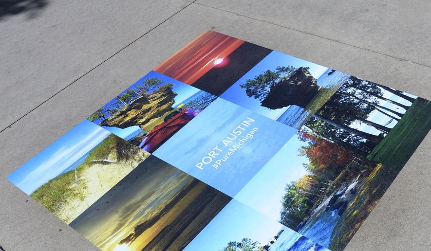 In a May 22, 2015 photo, Detail of a grid of photos picturing sights around Port Austin on the Pure Michigan PhotoWalk in Detroit. Running along the riverfront, the display, which celebrates Pure Michigan reaching one million Facebook fans, features more than 1,000 images. Tourism officials with the Pure Michigan campaign believe this summer will be the best one yet when it comes to visitors coming to the state and bringing business. (Clarence Tabb Jr./The Detroit News via AP)
