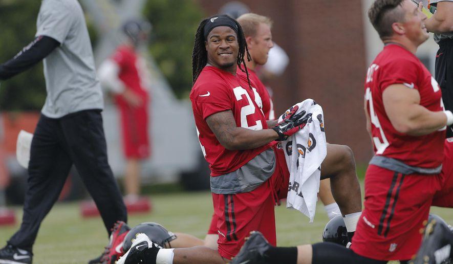 Atlanta Falcons running back Devonta Freeman (24) stretches during an offseason NFL football  training session Tuesday, May 26, 2015, in Flowery Branch, Ga.  (AP Photo/John Bazemore)