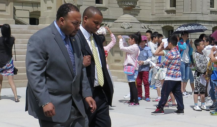State Rep. Fred Durhal, left, escorts state Sen. Virgil Smith after a session at the State house in Lansing, Mich., Tuesday, May 26, 2015. Smith returned to work Tuesday, more than two weeks after being charged with three felonies in connection with a shooting incident at his home. The Detroit Democrat, who declined to answer questions from the media as he left the Senate chamber Tuesday, is facing the felonies and a misdemeanor in connection with a non-fatal shooting involving his ex-wife outside his Detroit home on May 10. (AP Photo/David Eggert)