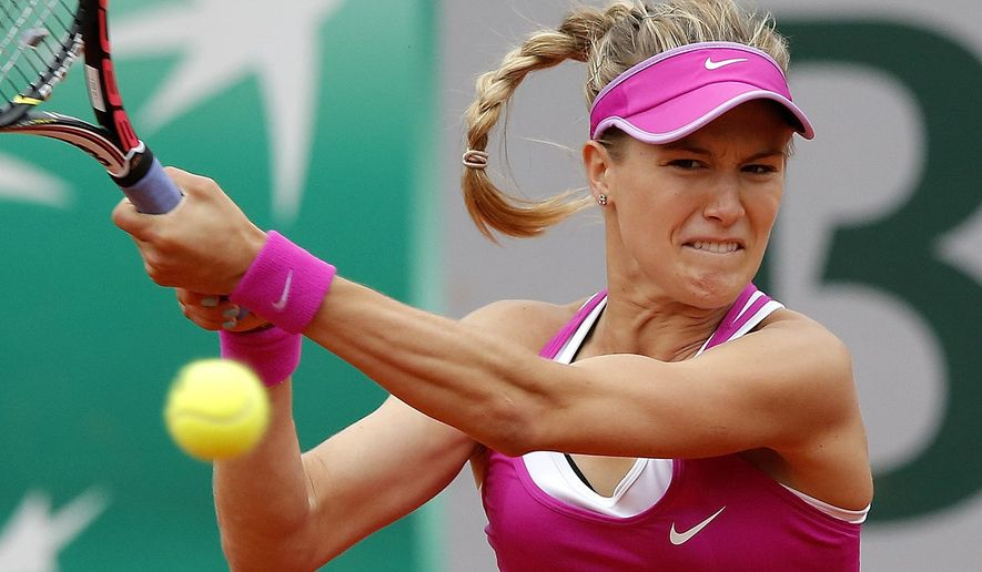 CAPTION CORRECTION, CORRECTS FINAL SCORE IN SECOND SENTENCE - Canada's Eugenie Bouchard returns the ball to  France's Kristina Mladenovic during their first round match of the French Open tennis tournament at the Roland Garros stadium, Tuesday, May 26, 2015 in Paris. Mladenovic won 6-4, 6-4. (AP Photo/Francois Mori)