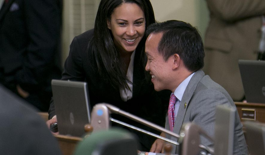 Assemblywoman Autumn Burke, D-Inglewood, talks with Assemblyman David Chiu, D-San Francisco, after their measure regulating pregnancy centers was approved by the Assembly in Sacramento, Calif., Tuesday May 26, 2015.The bill AB775 would require pregnancy centers to post notices saying that reproductive health services, including abortion, are available to pregnant women and may be financed under government programs. It would not require referrals to abortion clinics. The centers would also have to disclose if they are not medically licensed.  The legislation now goes to the Senate. (AP Photo/Rich Pedroncelli)
