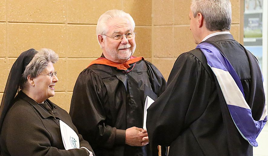 In a May 20, 2015 photo, Sister Colleen Ann Nagleo, left, Richard Dengate, center, speak with David Faber, superintendent of Catholic Schools, in Grand Rapids, Mich. Dengate, 77, graduated with West Catholic High School students. He dropped out of high school in 1954 after his sophomore year to enlist in the Air Force and served in Korea. The retired educator (high school and college teacher) wrote the principal requesting the diploma he missed out on. (Monica Scott/Grand Rapids Press via AP)