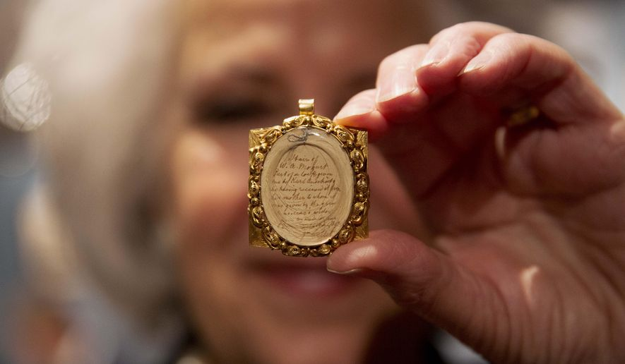 Gallery assistant Sandra Handley poses for photographs with a lock of Wolfgang Amadeus Mozart's hair, contained in a 19th-century gilt locket at the Sotheby's auction house in London, Tuesday, May 26, 2015.  The lock of hair is estimated to fetch 10,000 to 12,000 pounds ($15,383 to $18,459, euro14,109 to 16,931) as part of the Music, Continental and Russian Books and Manuscripts auction on Thursday May 28 in London.  (AP Photo/Matt Dunham)