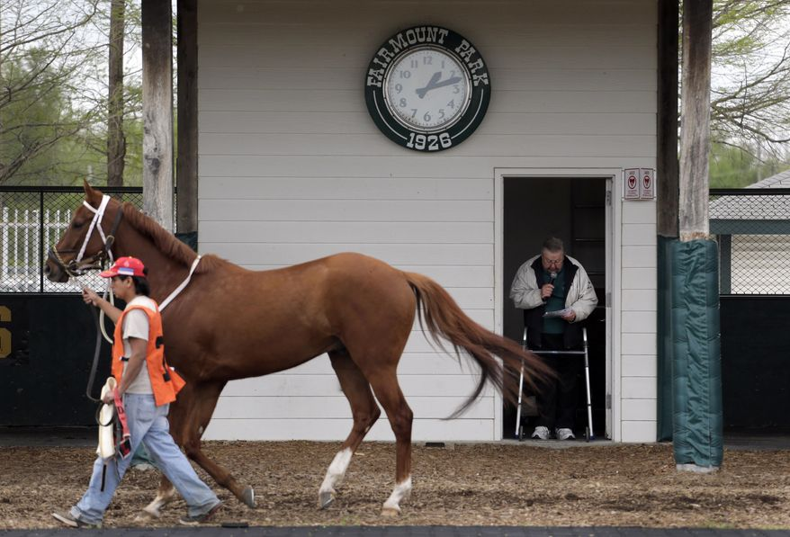 FILE - In this Tuesday, April 21, 2015, file photo, track handicapper Jay Randolph stands in a doorway with the aid of a walker and previews the field for an upcoming race for fans at Fairmount Park in Collinsville, Ill. The owners of an East St. Louis casino plan to purchase the struggling Fairmount Park racetrack, provided Illinois lawmakers agree to allow a gambling expansion that would bring slot machines to the state's five horse racing venues. Employee-owned CQ Holdings Inc., owner of the riverfront Casino Queen, announced a tentative agreement to buy the 90-year-old track located eight miles to the east in Collinsville Tuesday, May 26, 2015. (AP Photo/Jeff Roberson, File)