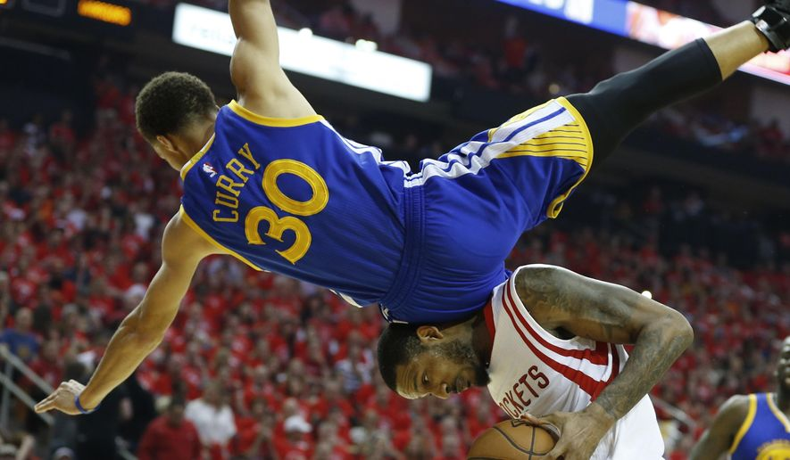Golden State Warriors guard Stephen Curry (30) topples over Houston Rockets forward Trevor Ariza (1) during the first half in Game 4 of the Western Conference finals of the NBA basketball playoffs, Monday, May 25, 2015, in Houston. (James Nielsen/Houston Chronicle via AP) MANDATORY CREDIT