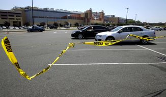 Crime scene tape blows in the wind near the scene of a fatal shooting in front of Resort World Casino in the borough of Queens in New York, Tuesday, May 26, 2015. The New York Police Department says a man suspected of killing his ex-girlfriend outside a casino has been shot to death by police. (AP Photo/Seth Wenig)