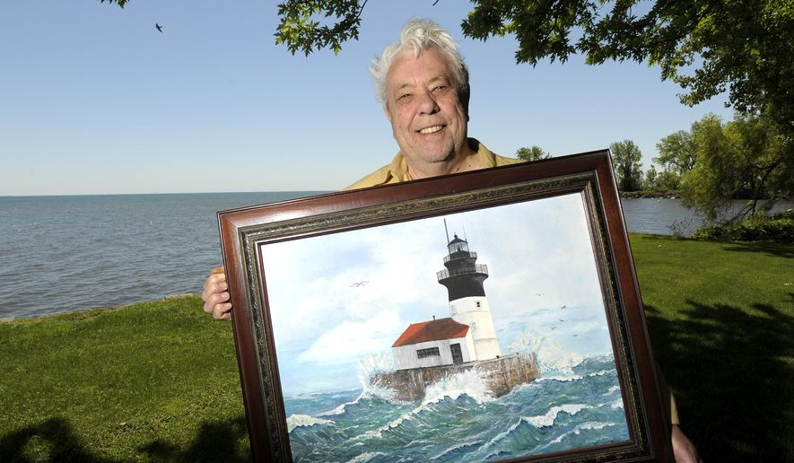 In a May 22, 2015 photo, Vietnam veteran Humphrey Macdonald, of Brownstown Twp., Mich.,poses with a painting of the Detroit River Lighthouse that he hand drew and painted in 2005. The U.S. General Services Administration (GSA) is looking for stewards for historic lighthouses in an effort to save tax dollars while preserving the past. As part of the National Historic Lighthouse Preservation Act (NHLPA), the agency is offering three historic lighthouses in Michigan at no cost to eligible state or local governments, nonprofit corporations, historic preservation groups, or community development organizations. (Todd McInturf/The Detroit News via AP)