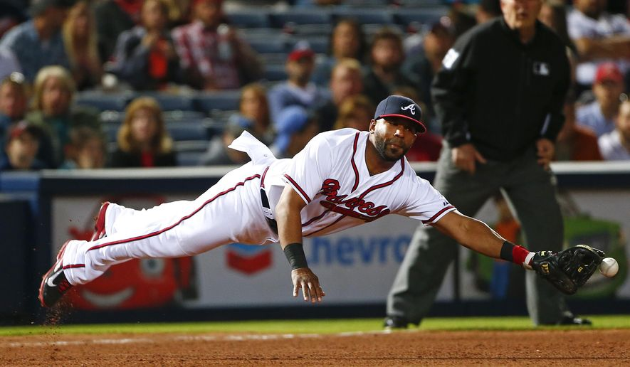 FILE - In this May 1, 2015, file photo, Atlanta Braves third baseman Alberto Callaspo reaches for a single by Cincinnati Reds' Zack Cozart during a baseball game in Atlanta. A proposed multiplayer trade between the Los Angeles Dodgers and Braves that would have sent third baseman Juan Uribe to Atlanta and Callaspo to Los Angeles has been vetoed by Callaspo. (AP Photo/John Bazemore, File)