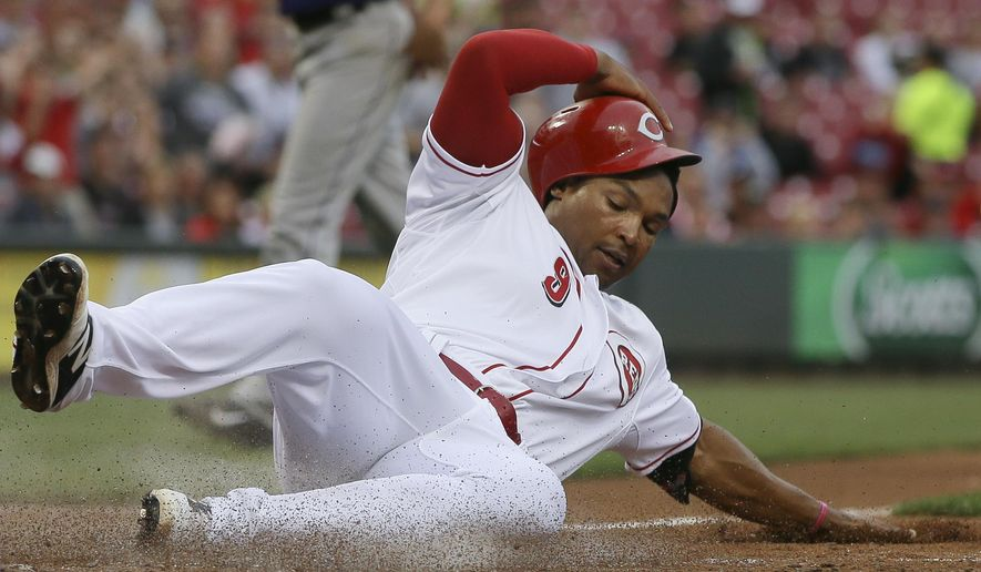 Cincinnati Reds' Marlon Byrd slides home to score on a single by Billy Hamilton in the second inning of a baseball game against the Colorado Rockies, Tuesday, May 26, 2015, in Cincinnati. (AP Photo/John Minchillo)