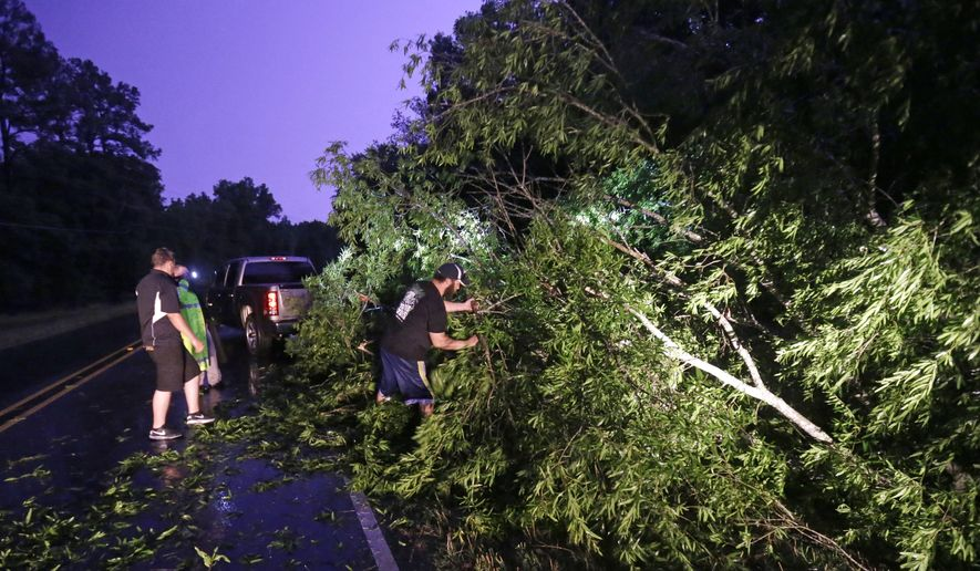 Passers-by help a Caddo Parish Sheriff  push a tree out of the roadway on Linwood Ave., after a fast moving line of thunderstorms passed through in Shreveport, La., Monday, May 25, 2015. (AP Photo/Gerald Herbert)