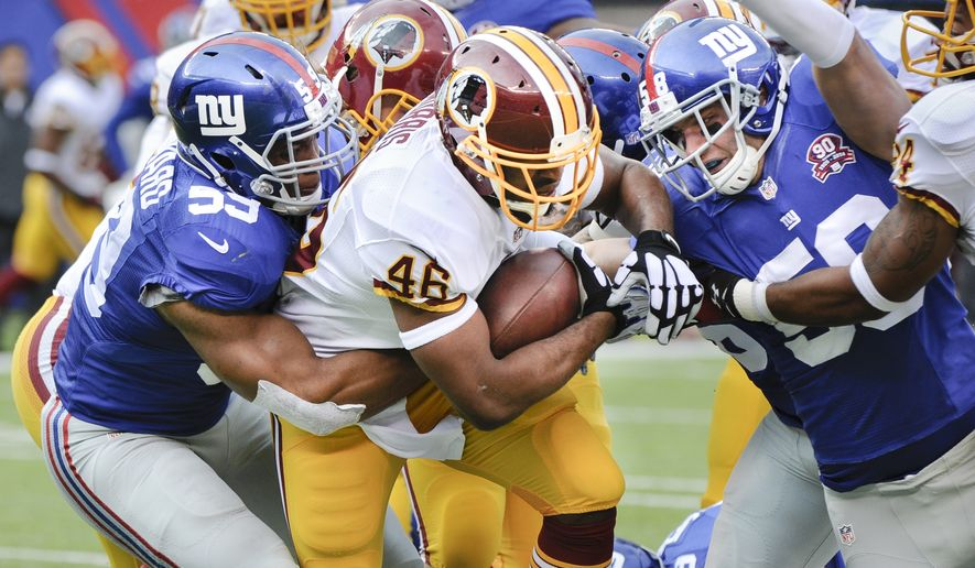 Washington Redskins running back Alfred Morris (46) is tackled by =New York Giants outside linebacker Devon Kennard (59) and New York Giants outside linebacker Mark Herzlich (58) during the second quarter of an NFL football game, Sunday, Dec. 14, 2014, in East Rutherford, N.J. (AP Photo/Bill Kostroun)