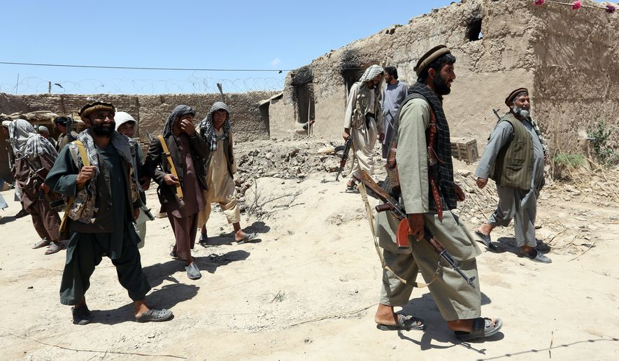 In this Thursday, May 21, 2015 photo, local militia group fighters walk past a building torched by Taliban fighters at Talawka village in Kunduz province, north of Kabul, Afghanistan. Fighting has been raging in Kunduz for more than a month. Pushed back by army reinforcements that arrived days after the assault began, insurgents now occupy villages in Gor Tepa, 15 kilometers (12 miles) from the provincial capital, also called Kunduz. (AP Photo/Rahmat Gul)