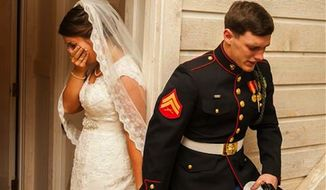 A photo U.S. Marine Cpl. Caleb Earwood holding his bride-to-be's hand in prayer has gone viral after it was posted online by the wedding photographer. (Dwayne Schmidt Photography via ABC News)