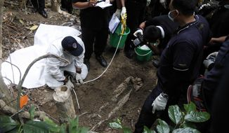 Malaysian police forensic team members inspect a freshly exhumed human body from an unmarked grave in Wang Burma at the Malaysia-Thailand border outside Wang Kelian, Malaysia Tuesday, May 26, 2015. Malaysian authorities have found one corpse as they started digging for bodies at an abandoned jungle camp used by human traffickers on the border with Thailand. The discovery came as forensics teams began the grim task of exhuming nearly 140 suspected graves in the mountainous area where trafficking syndicates were known to hold migrants for ransom. (AP Photo/Joshua Paul)