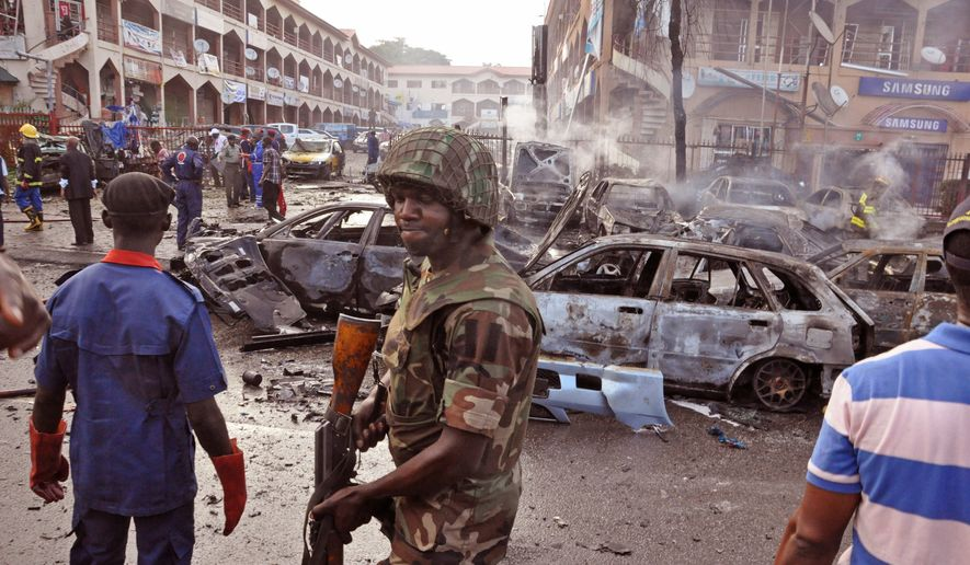 A Nigerian soldier walks at the scene of an explosion suspected to be set by a Boko Haram extremist in Abuja, Nigeria, on June, 25, 2014. (Associated Press) **FILE**