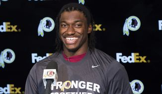 Washington Redskins quarterback Robert Griffin III smiles during a news conference after an NFL football organized team activity at Redskins Park, on Tuesday, May 26, 2015, in Ashburn, Va. (AP Photo/Evan Vucci)
