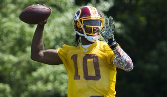 Washington Redskins quarterback Robert Griffin III throws a pass during an NFL football organized team activity at Redskins Park, on Tuesday, May 26, 2015, in Ashburn, Va. (AP Photo/Evan Vucci)