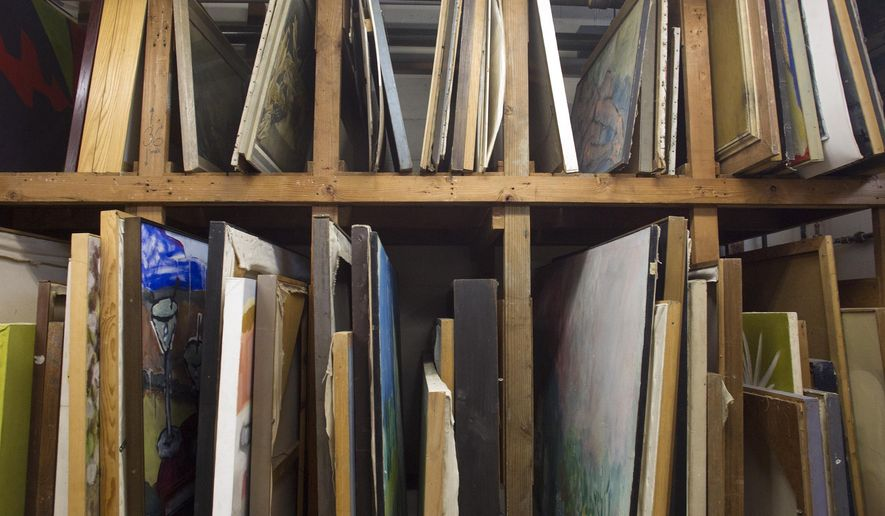 Art stacks up May 20, 2015, inside the University of Iowa Thesis Rental Gallery on the UI Research Park in Coralville, Iowa. The collection began in 1939, when graduating artists from the UI?s MFA program were required to leave their theses with the school. The requirement ended more than a decade ago but the gallery still receives donations. The art is available for rent to university employees and departments.  (David Scrivner /Iowa City Press-Citizen via AP)