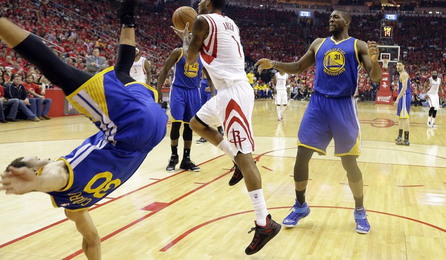 Golden State Warriors guard Stephen Curry (30) topples over Houston Rockets forward Trevor Ariza (1) during the first half in Game 4 of the Western Conference finals of the NBA basketball playoffs as center Festus Ezeli (31) looks on, Monday, May 25, 2015, in Houston. (AP Photo/David J. Phillip)